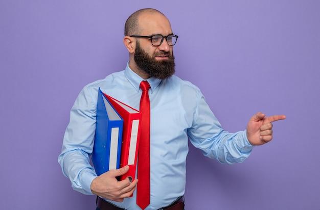 빨간 넥타이에 파란색 셔츠를 입은 수염 난 남자는 집게 손가락으로 옆을 가리키는 얼굴에 미소를 지으며 옆을 바라보고 있는 사무실 폴더를 들고 안경을 쓰고 있습니다.