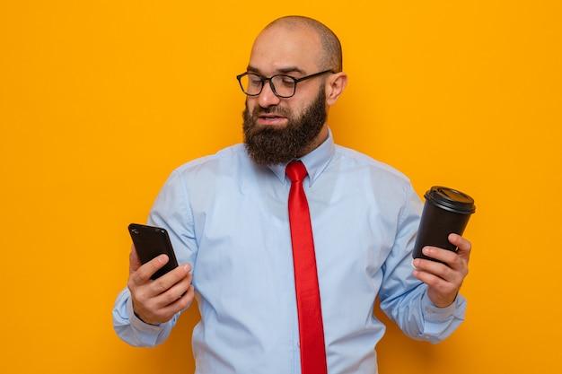 빨간 넥타이와 파란 셔츠를 입은 수염 난 남자는 스마트폰과 커피 컵을 들고 안경을 쓰고 주황색 배경 위에 행복하고 긍정적인 미소를 지으며 자신감을 갖고 서 있습니다.