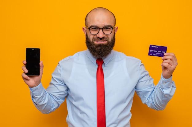 Бородатый мужчина в красном галстуке и синей рубашке в очках, держит смартфон и кредитную карту, выглядит счастливым и уверенным, улыбается уверенно