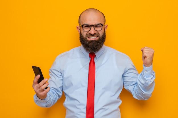 빨간 넥타이에 파란색 셔츠를 입은 수염 난 남자는 스마트폰을 들고 행복하고 흥분하여 승자처럼 주먹을 들고 있다