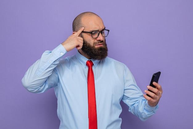 Бородатый мужчина в красном галстуке и синей рубашке в очках держит смартфон и недоуменно смотрит на него