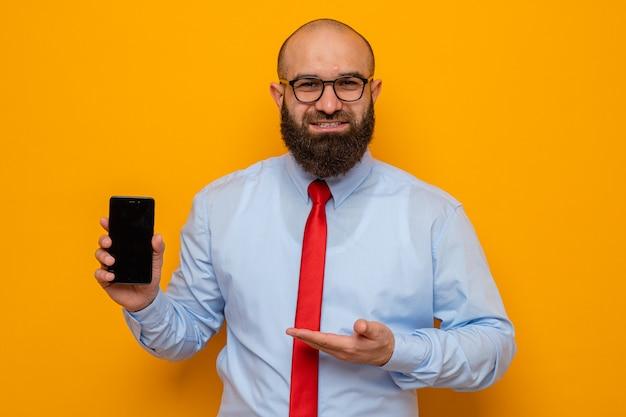 オレンジ色の背景の上に立っている彼の手の腕を提示するスマートフォンを保持している眼鏡をかけている赤いネクタイと青いシャツのひげを生やした男