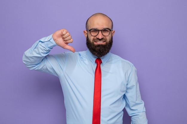 빨간 넥타이에 파란색 셔츠를 입은 수염 난 남자는 카메라를 바라보는 안경을 쓰고 행복하고 긍정적인 미소를 지으며 보라색 배경 위에 서 있는 자신을 즐겁게 가리키고 있습니다.