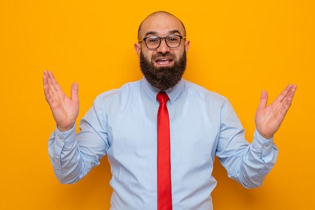 赤いネクタイと青いシャツを着たひげを生やした男は、オレンジ色の背景の上に立って元気に手を上げて幸せで前向きな笑顔のカメラを見て眼鏡をかけています