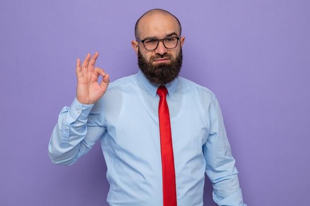 빨간색 넥타이와 파란색 셔츠를 입은 수염 난 남자는 행복하고 자신감이 있어 보이는 안경을 쓰고 ok 사인을 보여줍니다