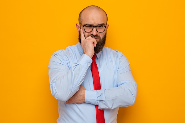 빨간 넥타이에 파란색 셔츠를 입은 수염 난 남자는 뺨에 손가락을 대고 진지한 얼굴로 안경을 쓰고 있다