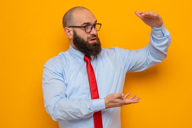 赤いネクタイと青いシャツを着たひげを生やした男は、オレンジ色の背景の上に立って幸せで驚きの手でサイズのジェスチャーを作る眼鏡をかけています