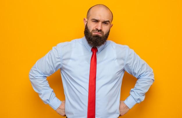 주황색 배경 위에 서 있는 얼굴에 회의적인 표정으로 카메라를 바라보는 빨간 넥타이와 셔츠를 입은 수염 난 남자