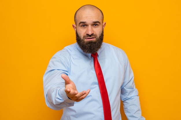 질문을 하려는 것처럼 팔을 들고 있는 빨간 넥타이와 셔츠를 입은 수염 난 남자