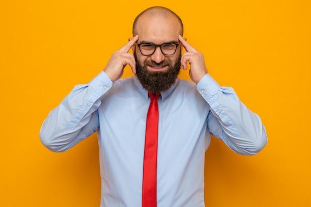 オレンジ色の背景の上に立っているタスクに集中している彼の寺院で人差し指で指しているカメラを見ている眼鏡をかけている赤いネクタイとシャツのひげを生やした男