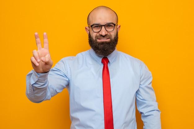 빨간 넥타이와 셔츠를 입은 수염 난 남자는 주황색 배경 위에 손가락이 서 있는 두 번째 숫자를 보여주며 자신감 있게 웃고 있는 카메라를 바라보며 안경을 쓰고 있습니다.
