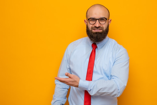 赤いネクタイとシャツを着たひげを生やした男は、オレンジ色の背景の上に彼の手立ちの腕でコピースペースを提示してカメラの笑顔を見て眼鏡をかけています