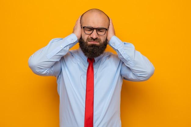 빨간 넥타이와 셔츠를 입은 수염 난 남자는 주황색 배경 위에 서 있는 강한 두통으로 고통스러워 보이는 그의 머리를 만지는 안경을 쓰고 있다
