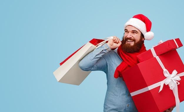 Бородатый мужчина в шляпе санты с бумажными пакетами и подарочными коробками