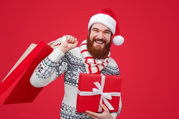 クリスマスプレゼントと買い物袋を保持しているサンタ帽子のひげを生やした男