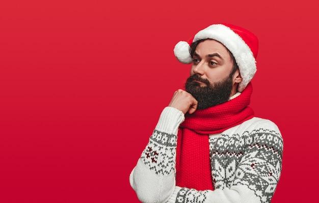 Бородатый мужчина в шляпе санта смотрит в сторону