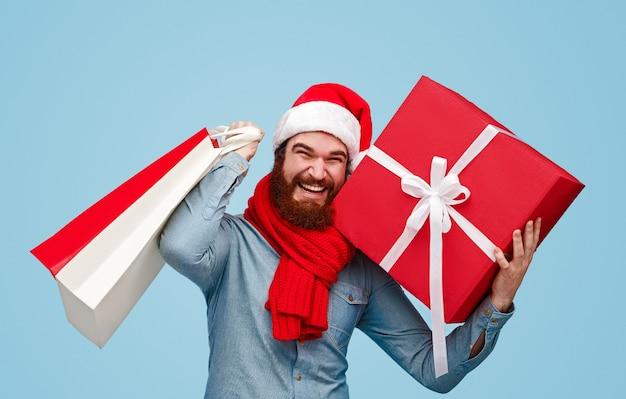 笑顔で買い物袋を運ぶサンタ帽子のひげを生やした男