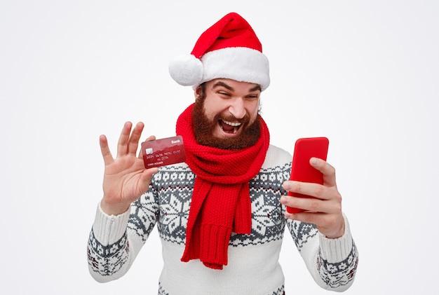 Бородатый мужчина в шляпе санта-клауса с помощью кредитной карты для оплаты покупок в интернете