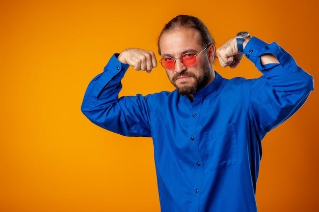Бородатый мужчина в рубашке показывает бицепс