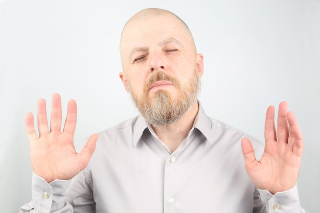 Бородатый мужчина в рубашке стоит с закрытыми глазами