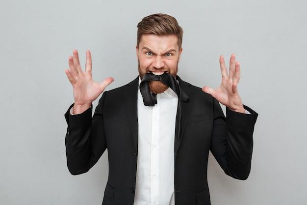 Бородатый мужчина в костюме позирует на сером фоне с галстуком
