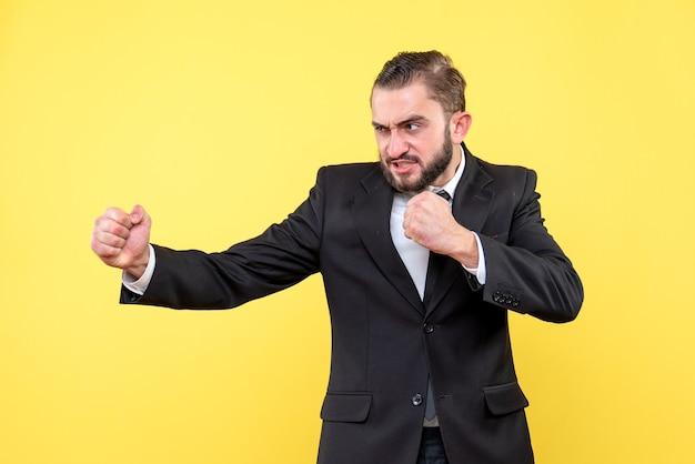 Бородатый мужчина в костюме, показывающий боксерские действия