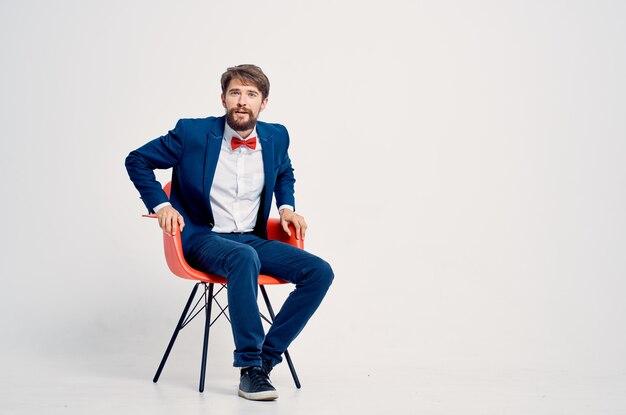 Бородатый мужчина в костюме, сидя на красном стуле, позирует профессионально