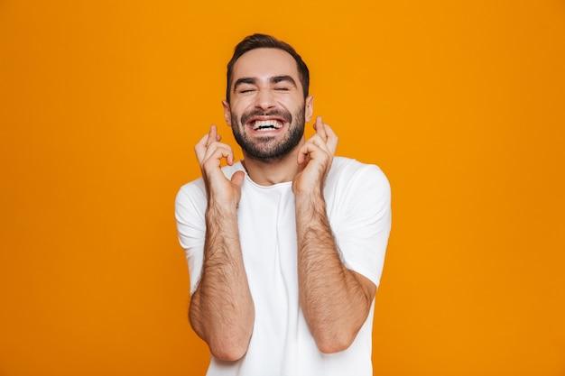 Бородатый мужчина в футболке сжимает кулаки стоя, изолированный на желтом
