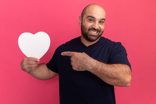 분홍색 벽 위에 서있는 행복한 얼굴로 웃고 검지 손가락으로 가리키는 골판지 심장을 들고 티셔츠에 수염 난 남자