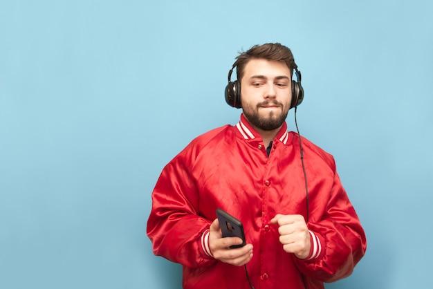 Бородатый мужчина в наушниках танцует со смартфоном в руке на синем