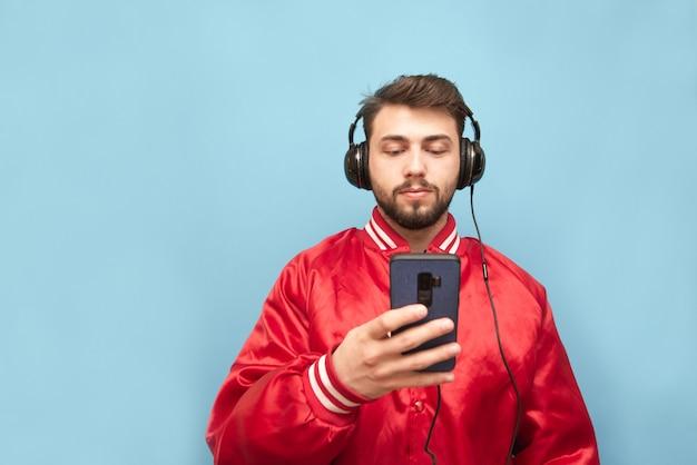 Бородатый мужчина в наушниках стоит на синей стене со смартфоном в руке