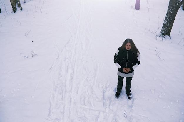 冬の森のひげを生やした男。あごひげを生やした魅力的な幸せな若い男が公園を散歩します。