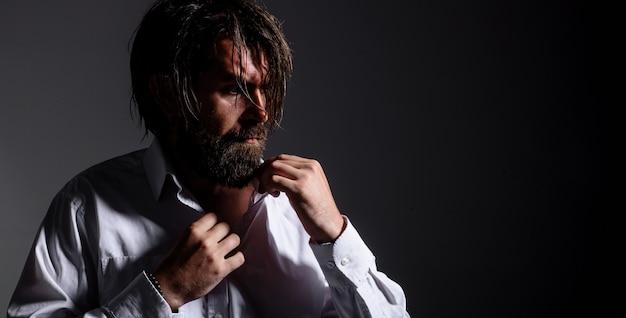 白いシャツのひげを生やした男。ファッション。流行りの服。ハンサムな男性のシルエット。広告用のスペースをコピーします。