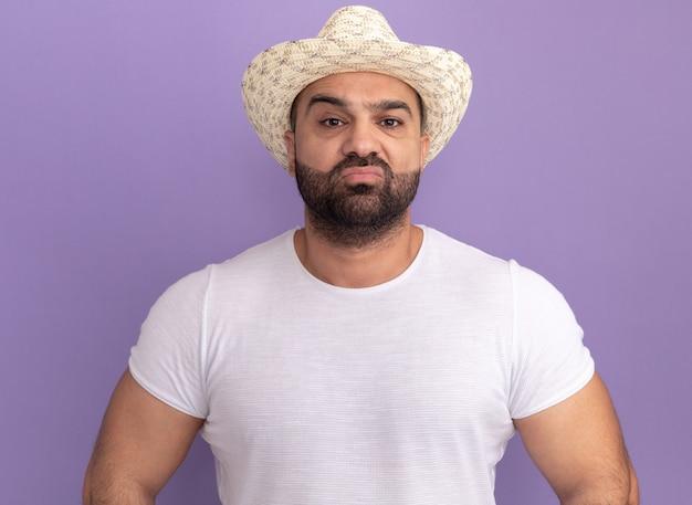 보라색 벽 위에 서 심각한 자신감 표정으로 흰색 티셔츠와 여름 모자에 수염 난된 남자