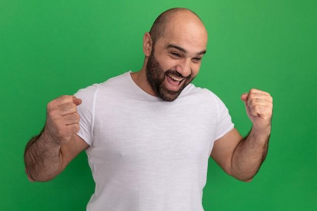 녹색 벽 위에 서있는 그의 성공을 기뻐하는 비명을 지르는 주먹을 떨리는 흰색 티셔츠에 수염 난 남자