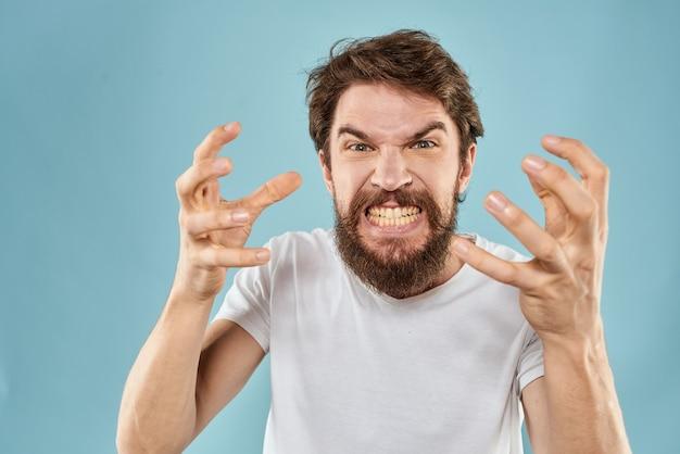 Бородатый мужчина в белой футболке эмоции жесты руками недовольное выражение лица синий фон