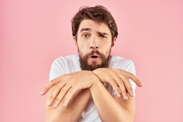 Бородатый мужчина в белой футболке жестикулирует изолированными руками