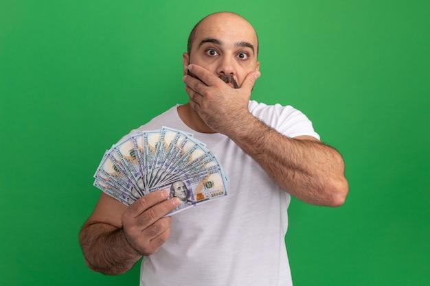 녹색 벽 위에 서있는 손으로 입을 덮고 충격을 받고 현금을 들고 흰색 티셔츠에 수염 난 남자
