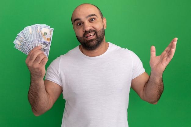 녹색 벽 위에 서 제기 팔에 행복하고 놀란 현금을 들고 흰색 티셔츠에 수염 난 남자