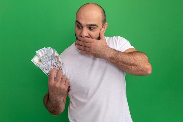 돈을보고 현금을 들고 흰색 티셔츠에 수염 난 남자는 녹색 벽 위에 서있는 손으로 입을 덮고 놀란 놀라움