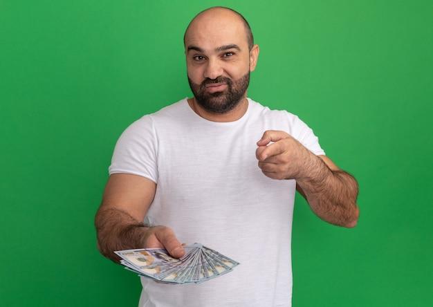 녹색 벽 위에 행복하고 긍정적 인 서 웃고 검지 손가락으로 현금을 가리키는 흰색 티셔츠에 수염 난된 남자