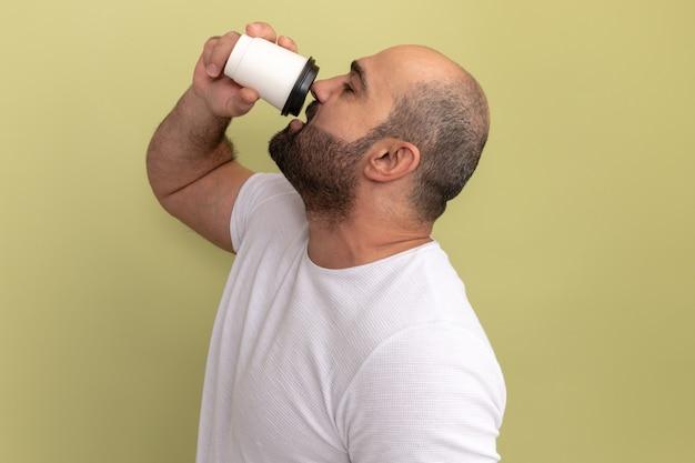 緑の壁の上に立って飲むコーヒーカップを保持している白いtシャツのひげを生やした男