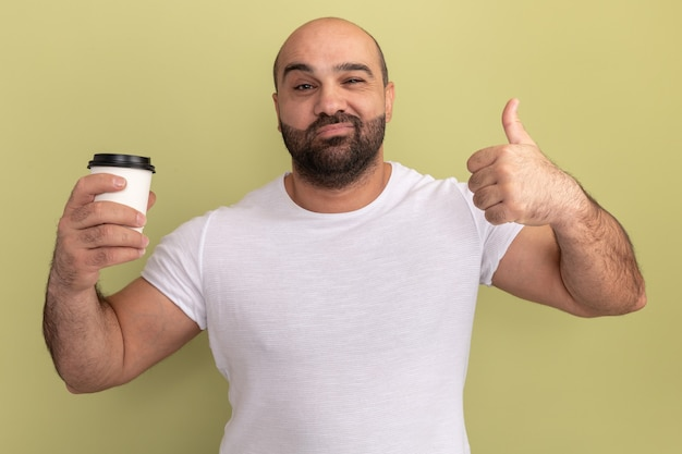 緑の壁の上に幸せで前向きなコーヒーカップを保持している白いtシャツのひげを生やした男
