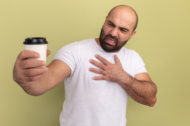 緑の壁の上に立っている嫌な表情でそれを見ているコーヒーカップを保持している白いtシャツのひげを生やした男