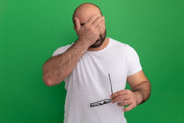 녹색 벽 위에 서있는 손으로 눈을 감고 안경을 들고 흰색 티셔츠에 수염 난된 남자