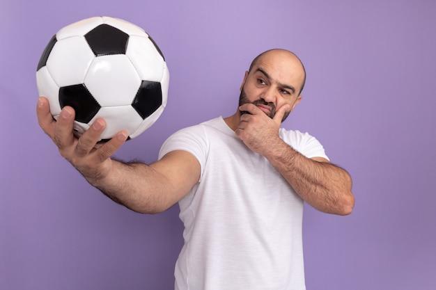 Бородатый мужчина в белой футболке держит футбольный мяч, глядя на него с задумчивым выражением лица, думая, стоя над фиолетовой стеной