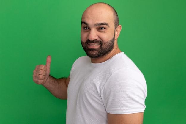 흰색 티셔츠에 수염 난된 남자 녹색 벽 위에 서있는 자신감을 보여주는 엄지 손가락 미소