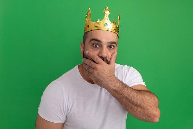 녹색 벽 위에 서있는 손으로 입을 덮고 충격을 받고 황금 왕관을 쓰고 흰색 티셔츠에 수염 난 남자