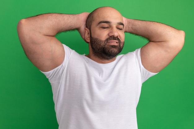 녹색 벽 위에 서있는 자신감있는 표정으로 그의 머리 뒤에 손으로 눈을 감고 흰색 티셔츠에 수염 난 남자