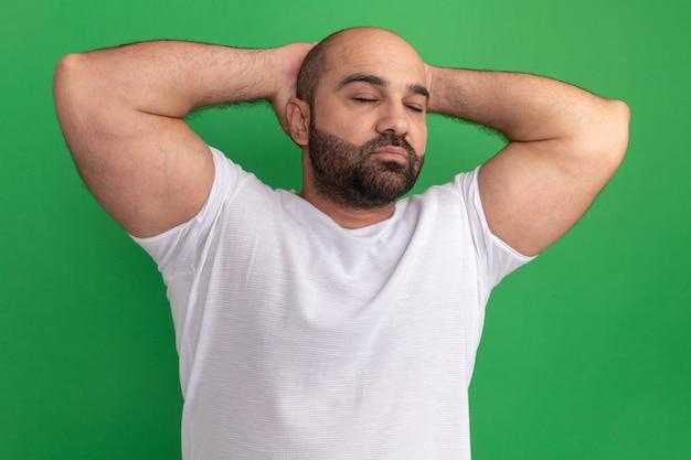 녹색 벽 위에 자신감 서 찾고 그의 머리 뒤에 손으로 닫힌 흰색 티셔츠에 수염 난된 남자